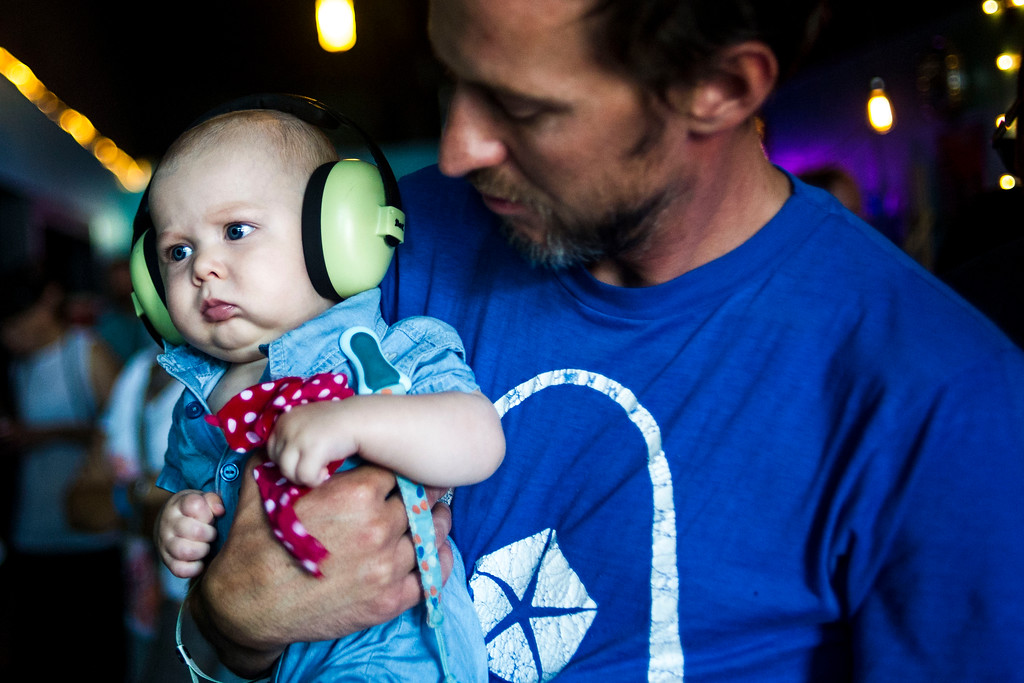 . Joseph Pope III holds his son, Joseph Pope IV while indie-pop band South of France performs at the Underground Music Showcase at Hi-Dive Bar on Sunday, July 27, 2014 in Denver, Colorado.   The four day music festival, which features more than 400 bands playing at venues along South Broadway wraps up today. (Photo by Kent Nishimura/The Denver Post)