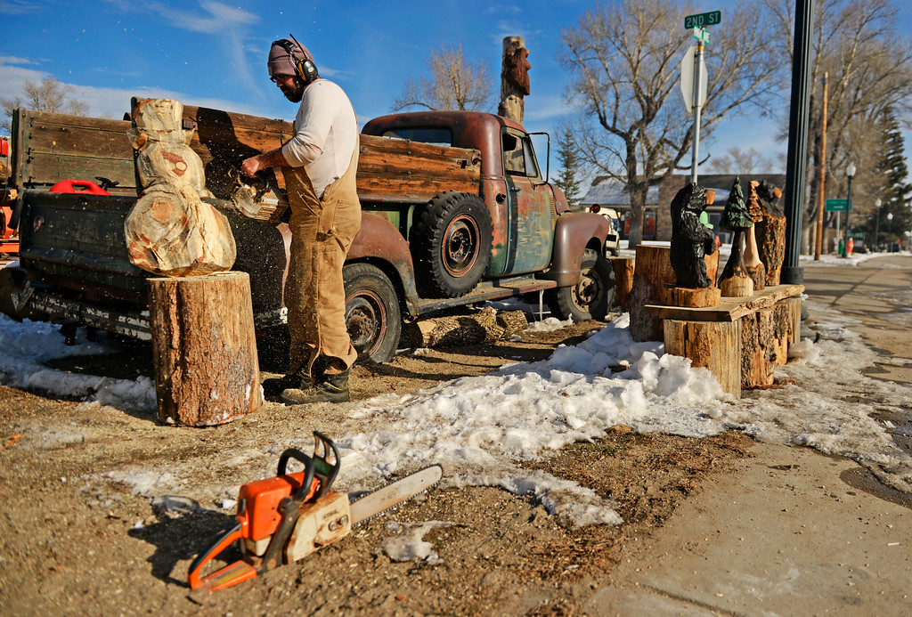 . Mark Mahorney carves a wooden snowman outside his business in Kremmling, December 19, 2013. The holiday snowman carving will include a top hat and scarf.  (Photo by RJ Sangosti/The Denver Post)