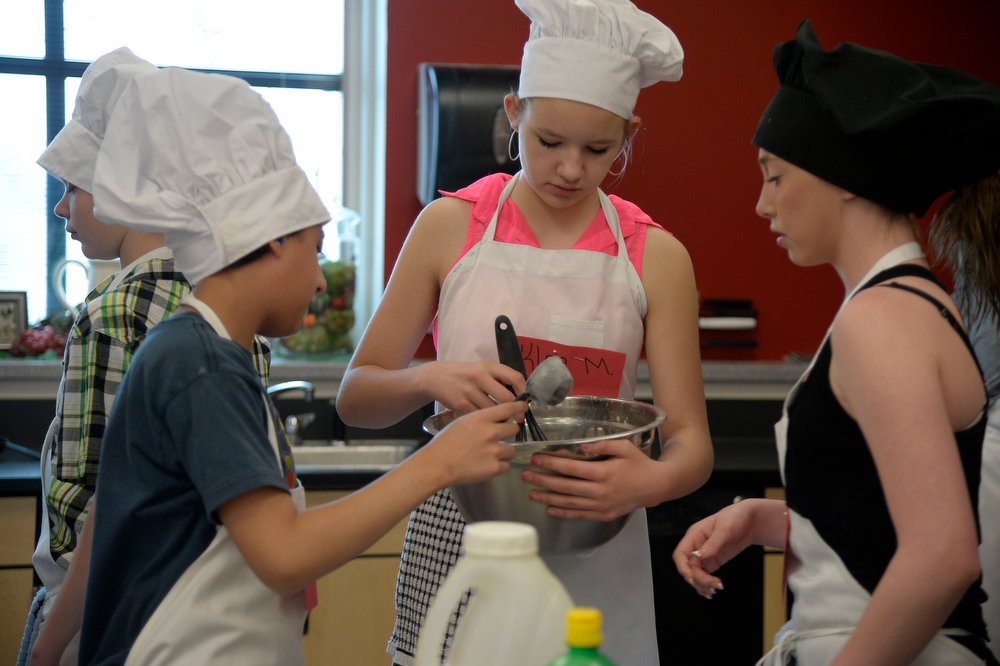 . John Paul  (L) helps Kloe Moore with the dough for their recipe as Sierra Lanham (R) looks on during the Culinary Arts for Kidz cook off April 2, 2014 at Cresthill Middle School. (Photo by John Leyba/The Denver Post)