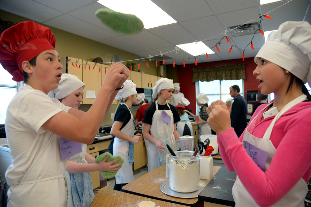 . Sebastian Fiueroa (L) and Ellie Sherbert toss their dough in the air to shape it during the Culinary Arts for Kidz cook off April 2, 2014 at Cresthill Middle School. The students were challenged to utilize one of the dough recipes previously taught during the quarter and modify and enhance the original recipe to create their own unique take of that specific recipe. The group was given 60 minutes to prepare, cook and present it to the judges. (Photo by John Leyba/The Denver Post)