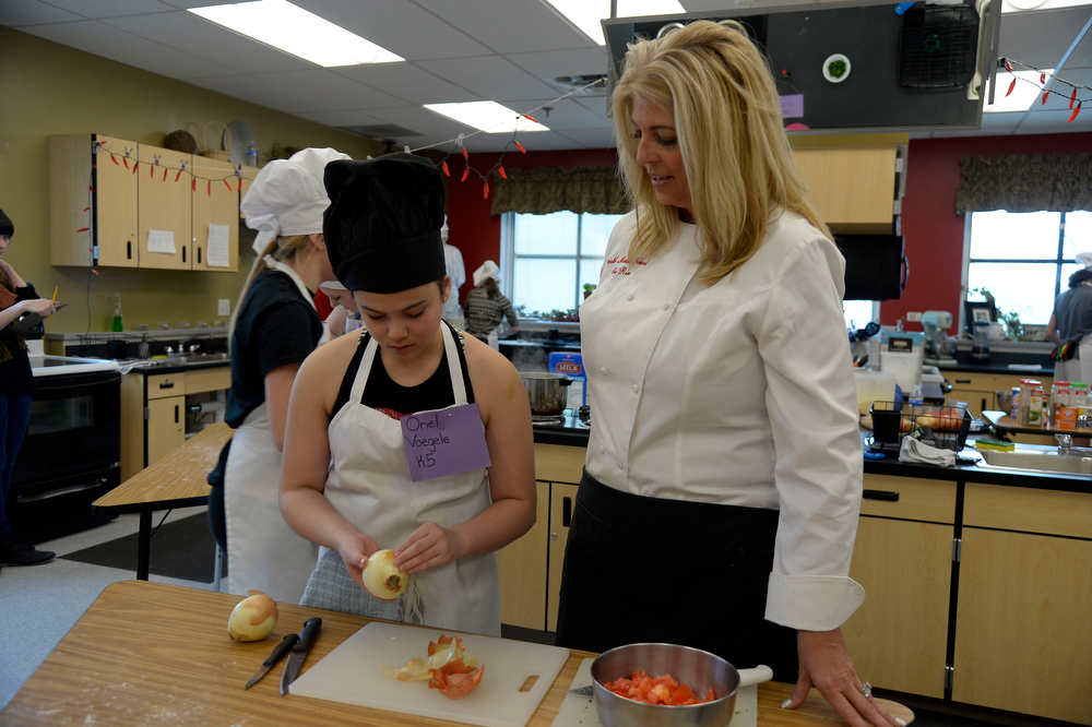 . Consumer & Family Studies teacher Mrs. Tomczak carefully watches over Oriel Voegele as she peels off the skin from an onion during the Culinary Arts for Kidz cook off April 2, 2014 at Cresthill Middle School. (Photo by John Leyba/The Denver Post)