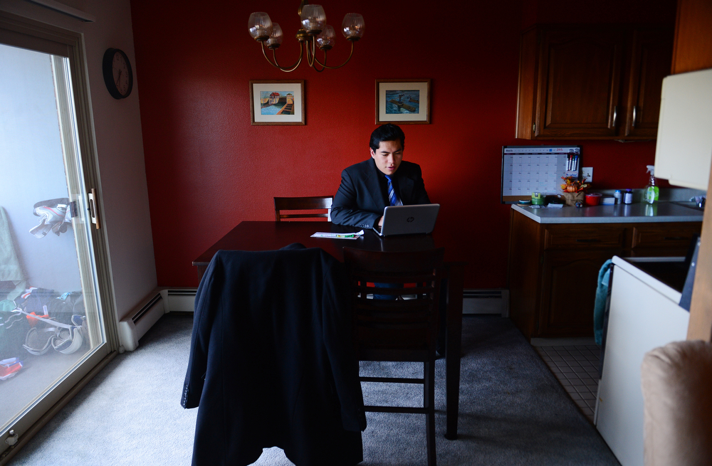 . Former foster care kid Diego Conde, 18, checks his computer before heading off for a busy day in Denver, Co on March 21, 2014. (Photo By Helen H. Richardson/ The Denver Post)