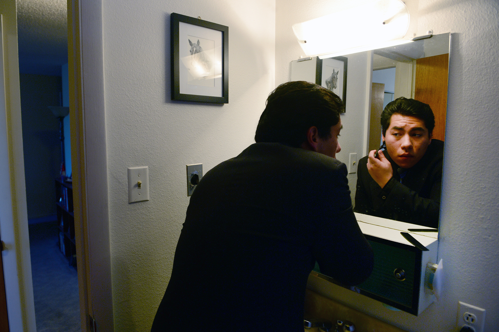 . Former foster care kid Diego Conde, 18, does a touch up shave before heading off for a busy day in Denver, Co on March 21, 2014. (Photo By Helen H. Richardson/ The Denver Post)