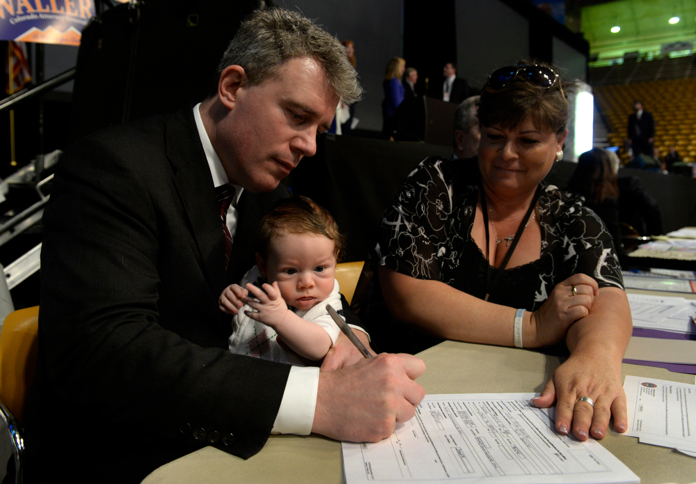 . Lana Fore-Warkocz, secretary for the state Republican party, right, holds official paperwork for Secretary of State Scott Gessler (holding 3-month-old son, Eric) as he is accepted as a Republican candidate for governor of Colorado. The Colorado Republican Party holds its state assembly for statewide candidates running for office at the Coors Event Center on the University of Colorado campus in Boulder. (Kathryn Scott Osler, The Denver Post)