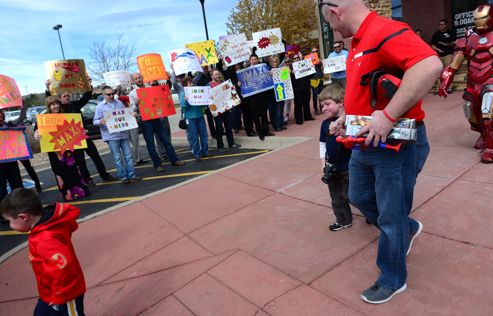. Max Vertin, 8,  of Hastings, Nebraska, holding the hand of his father Jason, right, walked out of the SkyVenture Colorado indoor sky diving to the cheers of supporters from local software firm Intuit in Lone Tree, Co  on April 15, 2014. (Photo By Helen H. Richardson/ The Denver Post)