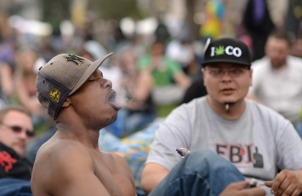 . Anthony Parker from New York, left, is smoking marijuana during the first day of the 420 Rally weekend in Civic Center Park, Denver, Colorado, April 19, 2014.  (Photo by Hyoung Chang/The Denver Post)