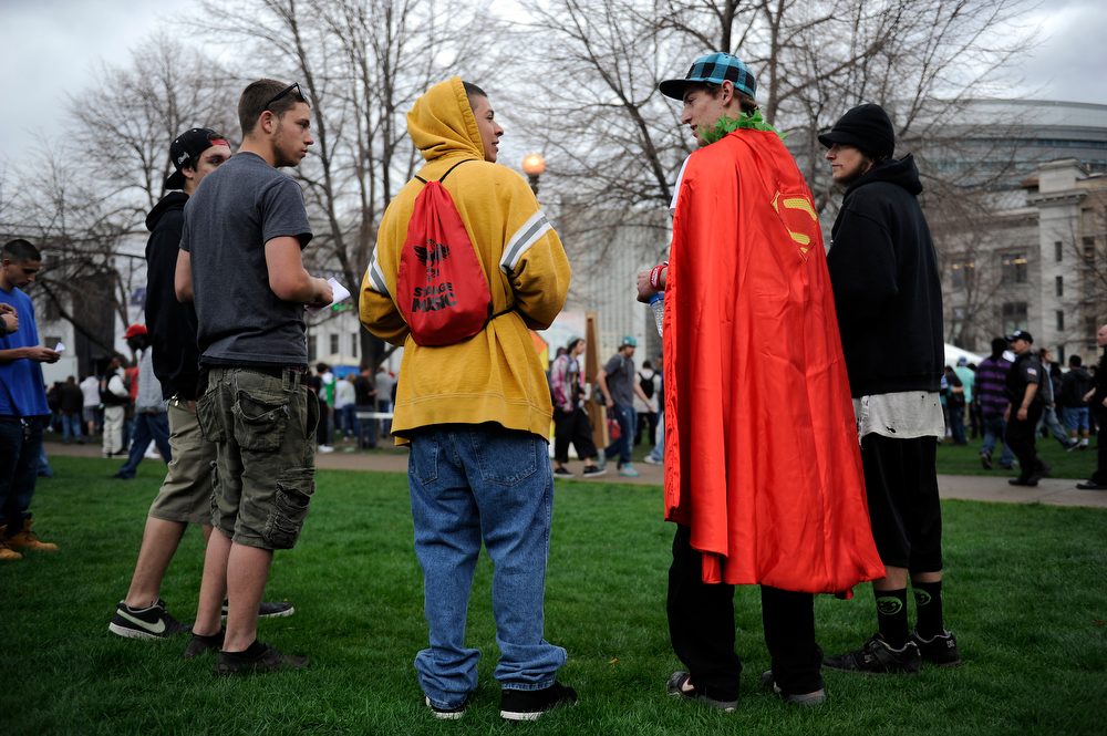 . JR Turner, 19, of Denver, sports a superman cape and marijuana leaf necklace as he chats with friends while Wyclef Jean plays during the 420 Rally at Civic Center Park in Denver, Colorado on April 19, 2014. (Photo by Seth McConnell/The Denver Post)