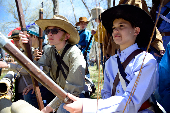 . Daniel Hensel, left, and Kanin Mcguire, play Confederate soldiers waiting for battle as 400 eighth-grade students from Adams 12 School District reenact scenes from the Battle of Spotsylvania and the Battle of Cold Harbor during Century Middle School\'s annual Civil War Reenactment at Lake Village Park in Thornton on Thursday, April 24, 2014. �You Can Live History,� a Colorado-based nonprofit, provided authentic uniforms and weaponry and filmed the battles. (Photo By Lindsay Pierce/The Denver Post)