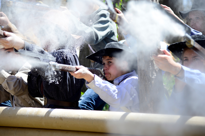 . Kanin Mcguire, center fires his gun, pretending to be a Confederate soldier as 400 hundred eighth-grade students from the Adams 12 School District reenact scenes from the Battle of Spotsylvania and the Battle of Cold Harbor during Century Middle School\'s annual Civil War Reenactment at Lake Village Park in Thornton on Thursday, April 24, 2014. �You Can Live History,� a Colorado-based nonprofit, provided authentic uniforms and weaponry and filmed the battles. (Photo By Lindsay Pierce/The Denver Post)
