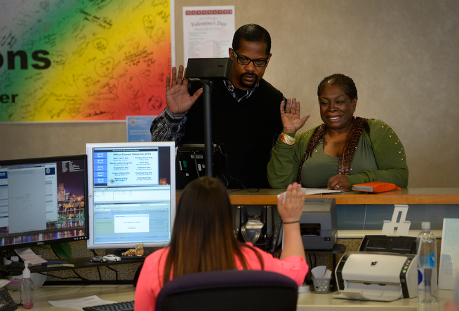 . Billy Wheelock, left,  and his fiancee, Berna Lang, right, take an oath administered by deputy clerk, Rachel Duran-Zimmer at the Denver Office of Clerk and Recorder Thursday afternoon, April 17, 2014, while picking up their marriage license. Earlier in the morning, Wheelock walked out of a Denver halfway house a free man after getting his ankle monitor cut off. Wheelock was granted clemency by the President of the United States after serving 21-years of a life sentence for drug charges occurred in Texas. (Photo By Andy Cross / The Denver Post)