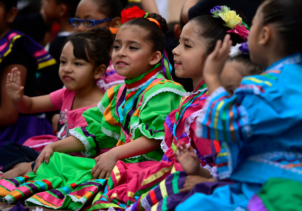 """. Young Members of the No Mo\' Violence Cultural Dance Group wave to crowds as they make their way down Lincoln Street. The 27th Annual Cinco de Mayo Festival kicks off with the \""""Celebrate Culture\"""" parade winding through downtown Denver and ending at the festival site in Civic Center Park. The event includes a green chile bowl cook off, a taco eating contest, chihuahua races, as well as cultural foods and musical and dance performances running through Sunday. (Kathryn Scott Osler, The Denver Post)"""