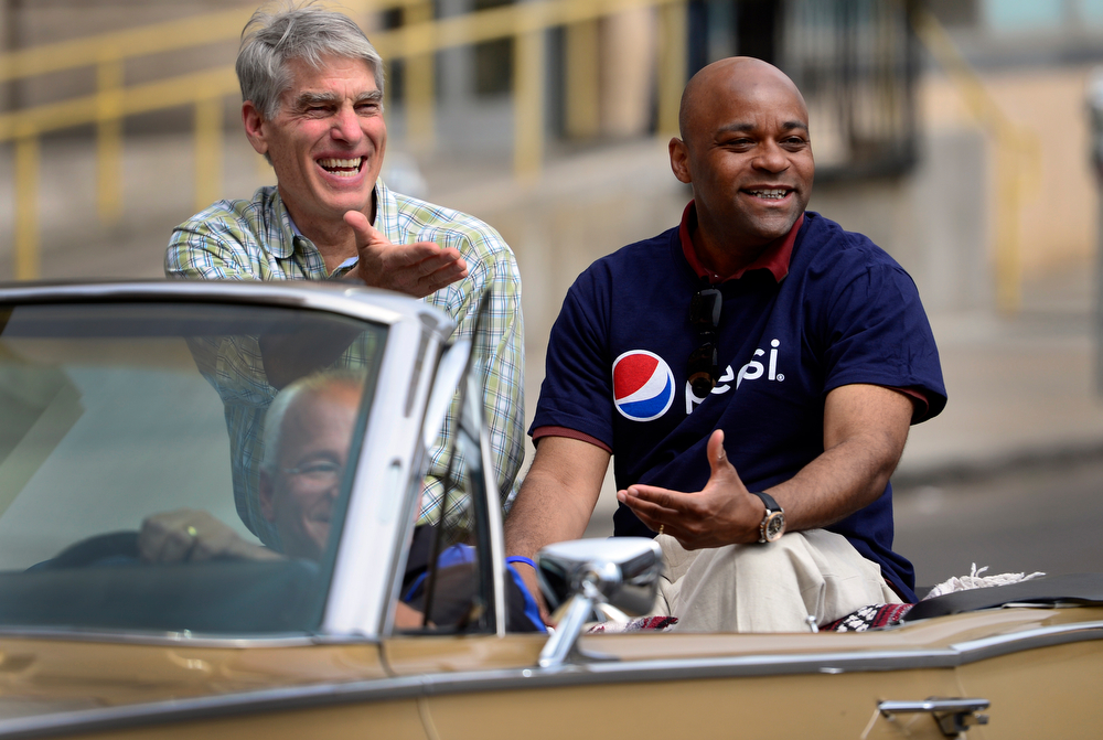 """. U.S. Senator Mark Udall, left, and Denver Mayor Michael Hancock help lead off the parade from the back of classic convertible. The 27th Annual Cinco de Mayo Festival kicks off with the \""""Celebrate Culture\"""" parade winding through downtown Denver and ending at the festival site in Civic Center Park. The event includes a green chile bowl cook off, a taco eating contest, chihuahua races, as well as cultural foods and musical and dance performances running through Sunday. (Kathryn Scott Osler, The Denver Post)"""