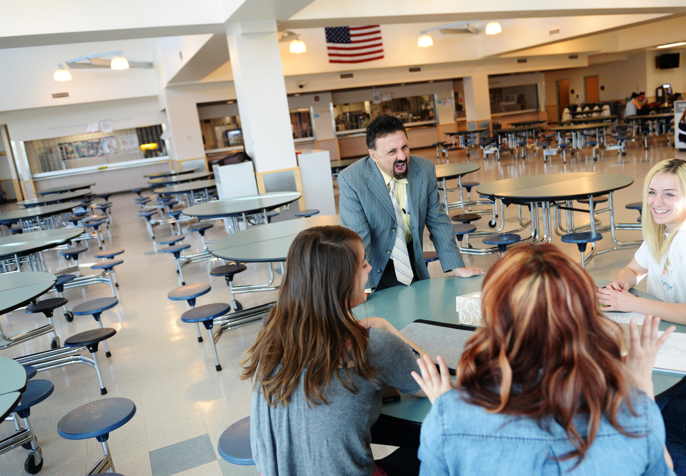 . Columbine High School Principal Frank DeAngelis jokes with students as they study for anatomy class in the lunch room of the school, Wednesday, April 16, 2014. DeAngelis makes a face when a student talks about a recent field trip to the morgue. (Photo by RJ Sangosti/The Denver Post)