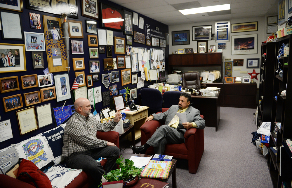 . Columbine High School Principal Frank DeAngelis, right, meets with choir teacher Lee Andres, Wednesday, April 16, 2014. DeAngelis\' office is covered in photos that show moments throughout his career at Columbine. (Photo by RJ Sangosti/The Denver Post)
