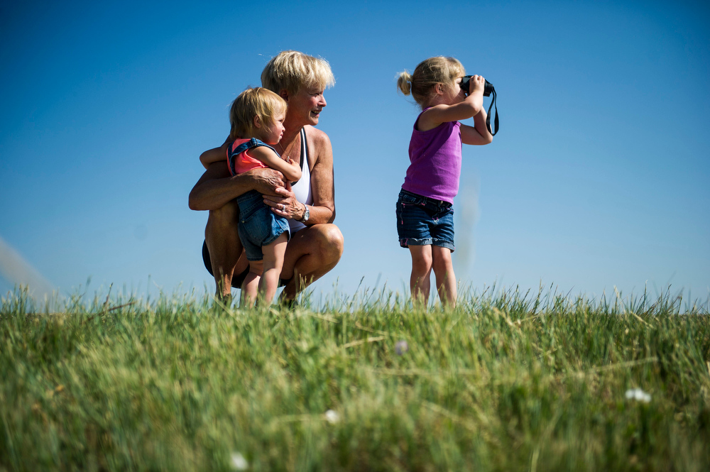 . Cathy Waters holds her granddaughter Triston Waters, 1, while Lyra Waters, 2, looks at a female eaglet who will soon be taking its first flight through binoculars along 120th Avenue near, E-470 where an eagles nest is located on Thursday, July 03, 2014 in Commerce City, CO.  Volunteers rotate in shifts to keep watch over the baby eagle, as it is expected to take flight soon, and it\'s nests proximity to E-470 tollway is worrisome. (Photo by Kent Nishimura/The Denver Post)