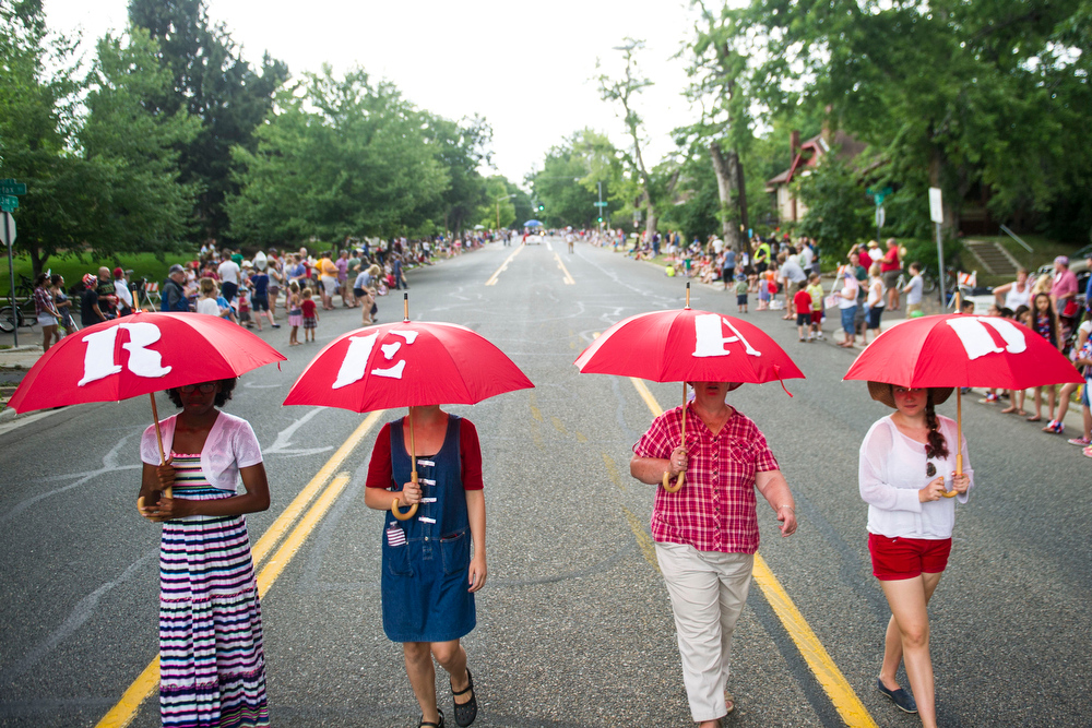 . Parade marchers hold umbrellas that spell Read in the 5th Annual July 4th Park Hill Parade along 23rd Avenue  on Friday, July 04, 2014 in Denver, CO.  The parade, which ran from Dexter Street to Krameria Street, featured marchers, marching bands, bikers, floats and classic cars.  (Photo by Kent Nishimura/The Denver Post)