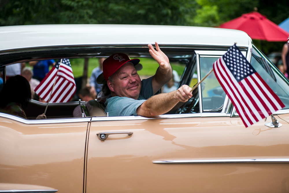 . Steven Rice waves out from his brothers car which was apart of the 5th Annual July 4th Park Hill Parade along 23rd Avenue  on Friday, July 04, 2014 in Denver, CO.  The parade, which ran from Dexter Street to Krameria Street, featured marchers, marching bands, bikers, floats and classic cars.  (Photo by Kent Nishimura/The Denver Post)