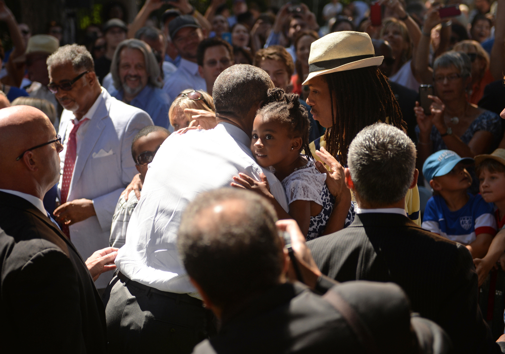 . A young girl hugs President Barack Obama after a speech at Cheesman Park in Denver, July 09, 2014. After the speech President Obama will attend a private luncheon at the Westin Denver Downtown hotel to raise money for U.S. Sen. Mark Udall\'s re-election campaign. (Photo by RJ Sangosti/The Denver Post)