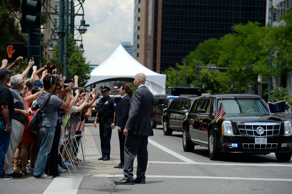 . A crowd gathers on the corner to get a glimpse of President Obama\'s motorcade leave the Westin Denver Downtown hotel July 9, 2014 where he was to raise money for U.S. Sen. Mark Udall\'s re-election campaign at a private luncheon at the Westin Denver Downtown hotel. (Photo by John Leyba/The Denver Post)