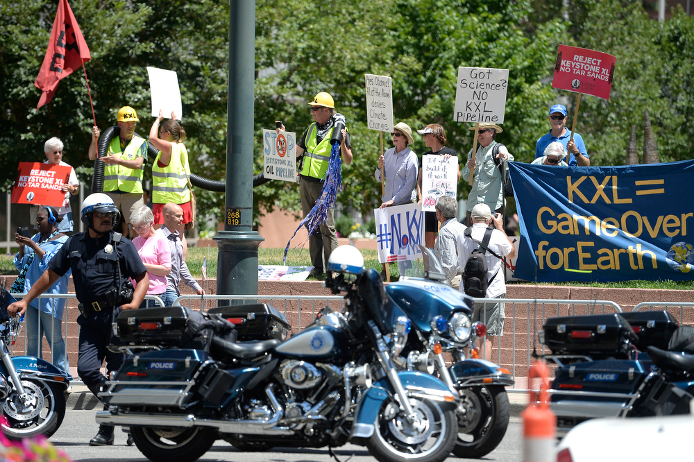 . Protesters gather across the street from the Westin Denver Downtown hotel July 9, 2014 where President Obama was to raise money for U.S. Sen. Mark Udall\'s re-election campaign at a private luncheon at the Westin Denver Downtown hotel. (Photo by John Leyba/The Denver Post)