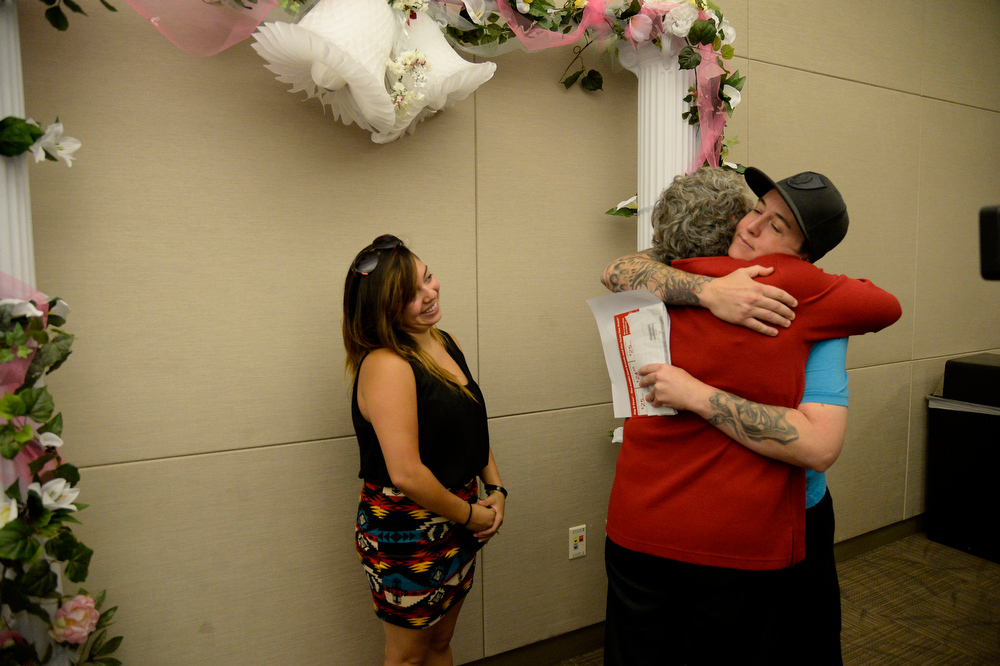 . Victoria Quintana looks on as Samantha Getman gets a hug from Clerk & Recorder Debra Johnson after receiving their marriage license. They were the first couple to arrive the Denver County clerk\'s office where they began issuing same sex marriage licenses July 10, 2014. They won\'t be official until they have a minister or official to sign the document and return it to the office to be recorded. (Photo by John Leyba/The Denver Post)