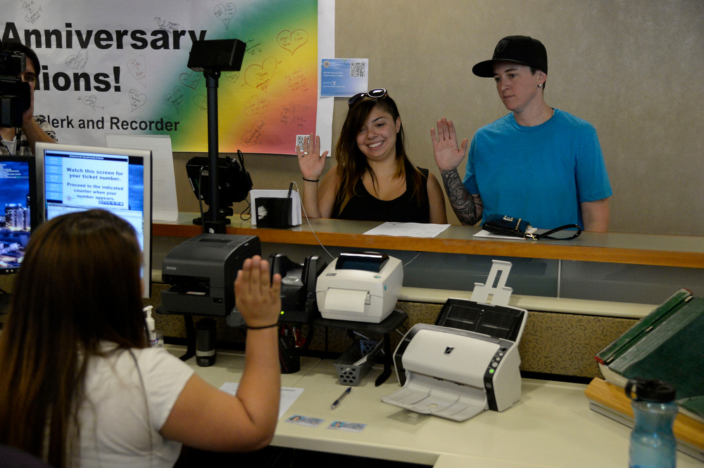 . Victoria Quintana (L) and Samantha Getman go through the oath process one step away from getting their marriage license. They were the first couple to arrive the Denver County clerk\'s office where they began issuing same sex marriage licenses July 10, 2014. (Photo by John Leyba/The Denver Post)