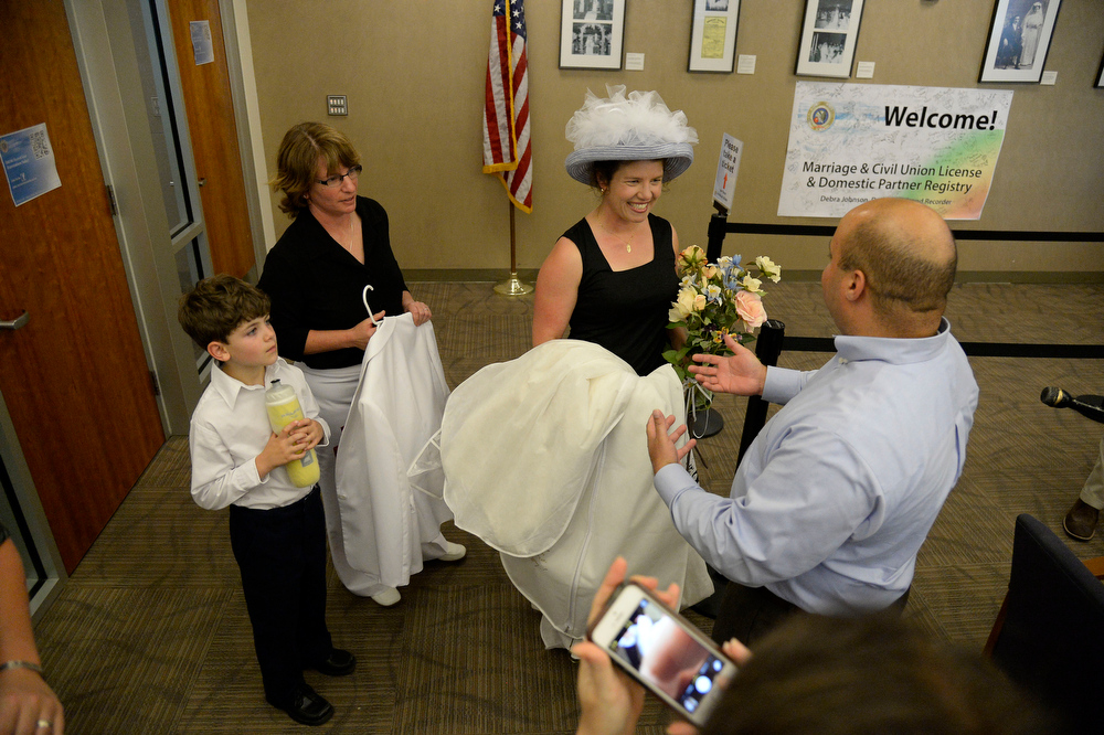 . Fran Simon (L) and Anna Simon are greeted by Juan Guzman, assistant Clerk & Recorder as they  arrive at the Denver County clerk\'s office where they began issuing same sex marriage licenses July 10, 2014. (Photo by John Leyba/The Denver Post)