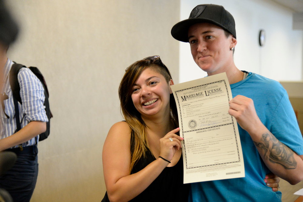 . Victoria Quintana (L) and Samantha Getman show off their marriage license. They were the first couple to arrive the Denver County clerk\'s office where they began issuing same sex marriage licenses July 10, 2014.  (Photo by John Leyba/The Denver Post)