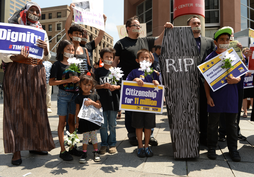 . Members of the Service Employees International Union, along with other community groups, hold a funeral march protesting Representatives Cory Gardner and Mike Coffman failure to pass immigration reform, July 15, 2014. The protester make their way down the 16th Street Mall  in downtown Denver. (Photo by RJ Sangosti/The Denver Post)