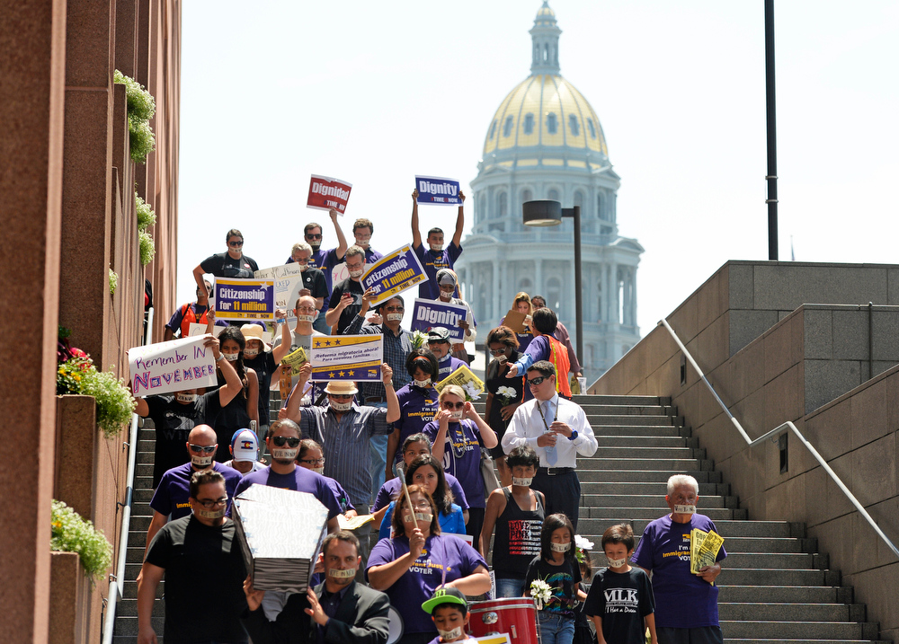 . Members of the Service Employees International Union, along with other community groups, hold a funeral march protesting Representatives Cory Gardner and Mike Coffman failure to pass immigration reform, July 15, 2014. The protester march in downtown Denver near the Colorado State Capitol. (Photo by RJ Sangosti/The Denver Post)