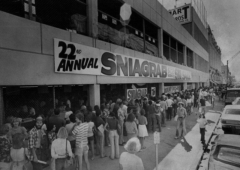 "Prospective buyers crowd the sidewalks along Broadway, waiting their turn to shop at the 22nd annual ""Sniagrab"" ski sale in 1976 staged by Gart Bros. Sporting Goods Co. The sale, which gets its title from the word bargains spelled  backwards, is housed this year in a new addition  to the main Gart store, 1000 Broadway. Credit: Denver Post"