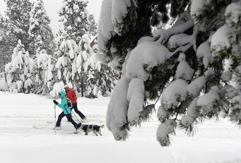 . Kestrel Neathawk, in blue, Sara Born, in red, and her dog Oliver get first tracks along Ridge Road as they enjoy the almost 2 feet of snow on April 16, 2016 in Nederland, Colorado. A spring storm dumped more than 2 feet of snow in the foothills and more is expected overnight.  (Photo by Helen H. Richardson/The Denver Post)