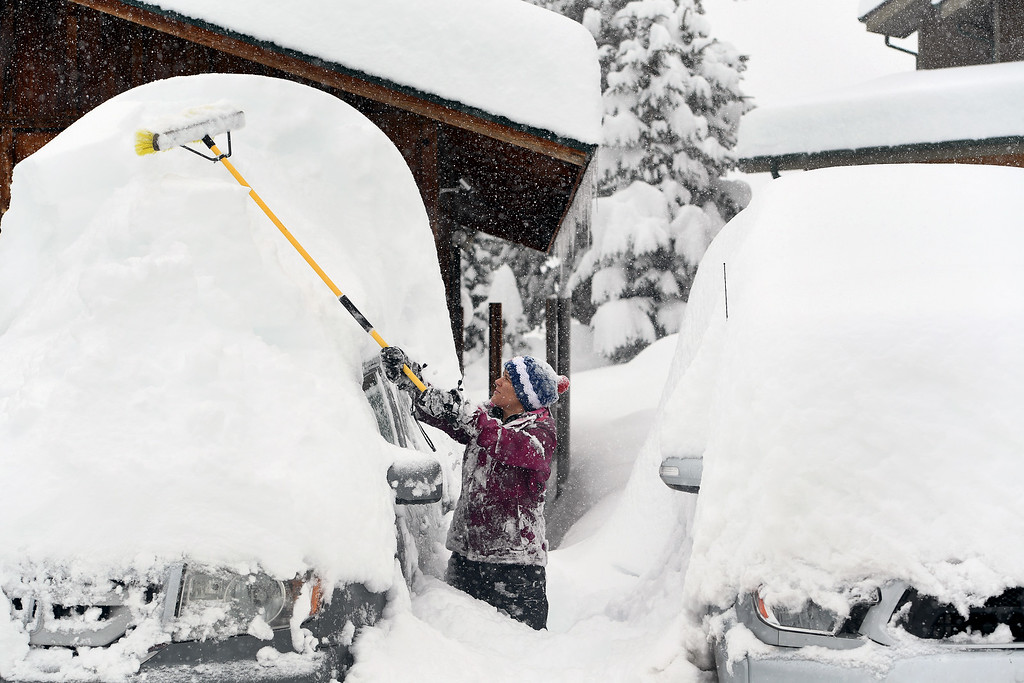 . NEDERLAND, CO - APRIL 17: Stephanie Weber, uses a large broom to clear the snow off of the family\'s cars on April 17, 2016 in Nederland, Colorado. A slow moving spring storm dumped almost 3 feet of snow over a two day period in the foothills. (Photo by Helen H. Richardson/The Denver Post)