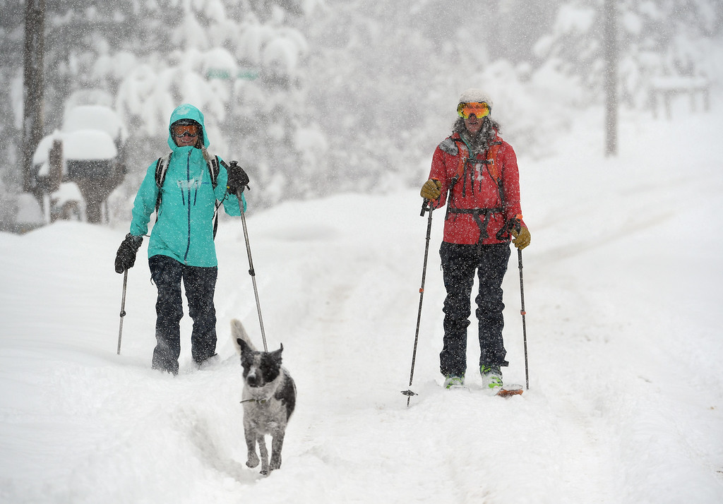 . Kestrel Hanson Neathawk, left, and Sara Born, right, with her dog Oliver, get first tracks along Ridge Road as they enjoy the almost 2 feet of snow on April 16, 2016 in Nederland, Colorado. A spring storm dumped more than 2 feet of snow in the foothills and more is expected overnight.  (Photo by Helen H. Richardson/The Denver Post)