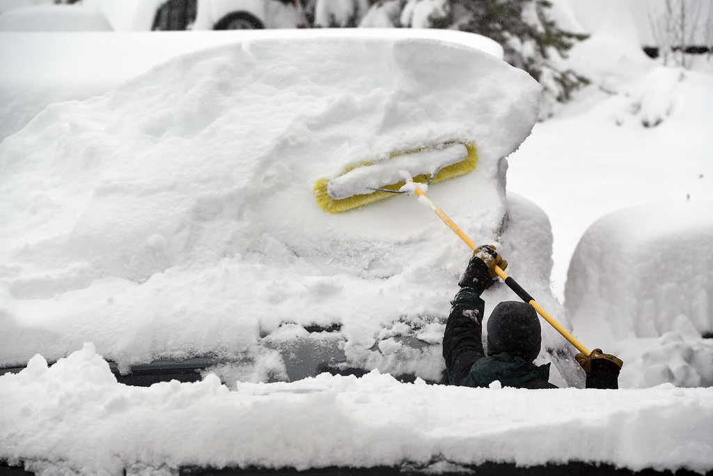 . NEDERLAND, CO - APRIL 17: Mark Weber, uses a large broom to clear the snow off of his wife\'s car  on April 17, 2016 in Nederland, Colorado. A slow moving spring storm dumped almost 3 feet of snow over a two day period in the foothills. (Photo by Helen H. Richardson/The Denver Post)