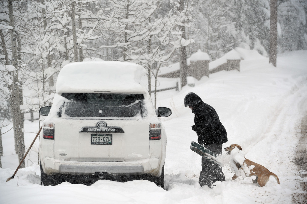 . Lauren Francis, with her dog Madison, digs out her car after almost 2 feet of snow fell in the area on April 16, 2016 in Nederland, Colorado. A spring storm dumped more than 2 feet of snow in the foothills and more is expected overnight.  (Photo by Helen H. Richardson/The Denver Post)