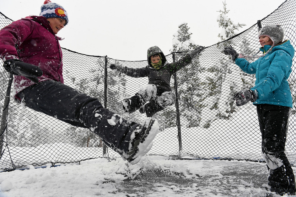 . NEDERLAND, CO - APRIL 17: Stephanie Weber, left, and her kids Ben, 8, middle, and Mackenzie, 10, right,  don\'t let the snow get in the way of their fun as they bounce on their trampoline on April 17, 2016 in Nederland, Colorado. A slow moving spring storm dumped almost 3 feet of snow over a two day period in the foothills. (Photo by Helen H. Richardson/The Denver Post)