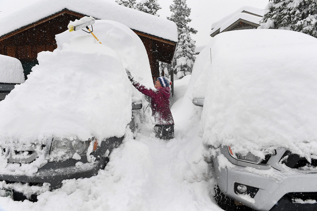 . NEDERLAND, CO - APRIL 17: Stephanie Weber, uses a large broom to clear the snow off of the family\'s car on April 17, 2016 in Nederland, Colorado. A slow moving spring storm dumped almost 3 feet of snow over a two day period in the foothills. (Photo by Helen H. Richardson/The Denver Post)