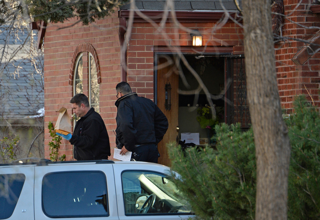 . In this April 15, 2014 photo, authorities investigate a homicide in Denver. Richard Kirk is being held for investigation of first-degree murder in the death of his wife in their Denver home. Police are investigating whether marijuana played a role in the killing. Police officers arrived just after Kristine Kirk was shot in the head Monday, April 14, 2014, about 15 minutes after she called 911. (AP Photo/The Denver Post, RJ Sangosti)