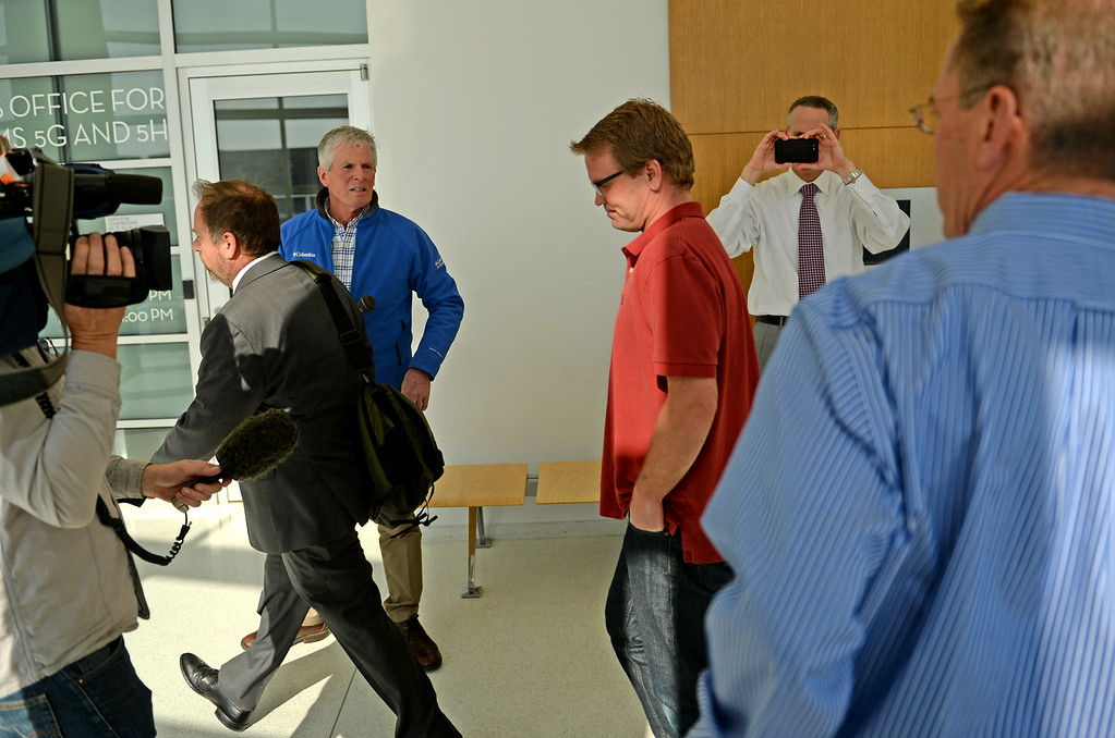 . Lance Kirk, center, walks past media after an advisement hearing in Denver District Court, for his brother, Richard Kirk, April 21, 2014. Richard Kirk, who allegedly shot and killed his wife after eating pot candy, faces one count of first-degree murder in the death of his wife, 44-year-old Kristine A. Kirk. (Photo by RJ Sangosti/The Denver Post)