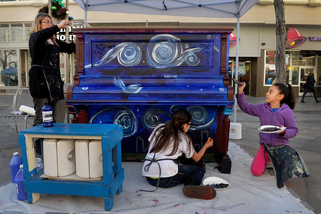 . (l-r)  Denver Center for International Studies Art Teacher Jessica Stellish works with students, Aaliyah Parra, 10, and Estefany Munoz, 9, while painting a piano on the 16th Street Mall in Denver, CO November 20, 2013. DCSI students volunteered to paint 5 pianos for the a public art installation, Your Keys to the City. The pianos will be unveiled on Thanksgiving and will be placed on the mall through the end of the year.  (Photo By Craig F. Walker / The Denver Post)