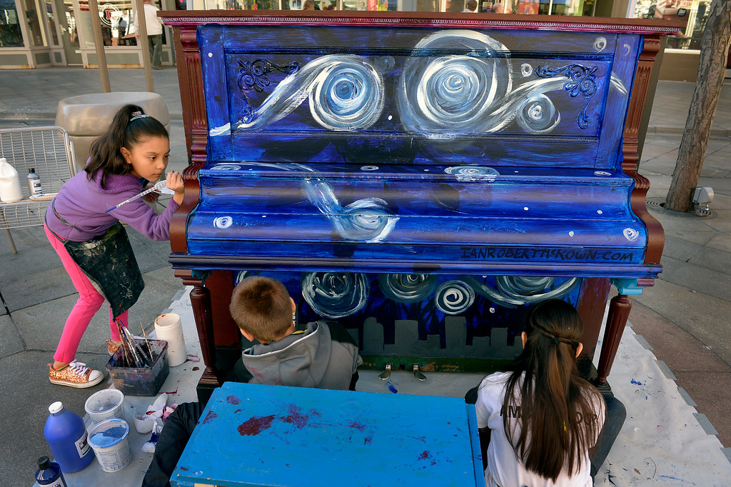 . (l-r)  Denver Center for International Studies fourth grader Estefany Munoz, left, joins her classmates in painting a piano on the 16th Street Mall in Denver, CO November 20, 2013. DCSI students volunteered to paint 5 pianos for the a public art installation, Your Keys to the City. The winter themed pianos will be unveiled on Thanksgiving and will be placed on the mall through the end of the year.  (Photo By Craig F. Walker / The Denver Post)