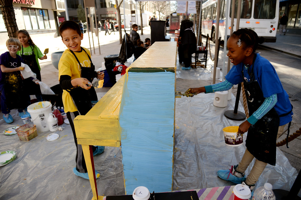 . Tae Hewitt, 9, right, Analytic Lopez, 9, front left, of Denver Center for International Studies at Fairmont are painting the piano on the 16th street mall. Denver, Colorado November 21, 2014. Elementary students from DCIS at Fairmont and Downtown Denver Expeditionary School are painting the town in holiday colors on the 16th Street Mall. A group of students, along with their teachers painted five pianos as part of the Downtown Denver Business Improvement District�s Your Keys to the City Program. (Photo by Hyoung Chang/The Denver Post)