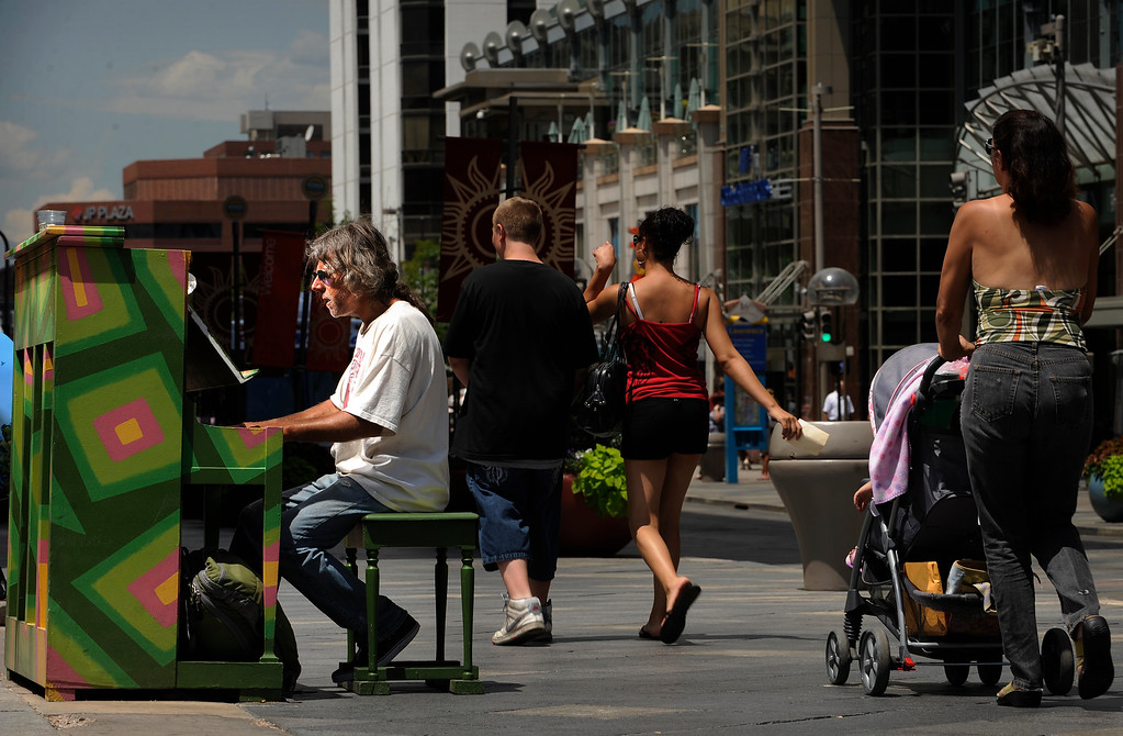 ". Visit with the many piano players that  play the pianos that are along 16th Street Mall in downtown Denver on Tuesday, July 19, 2011.  Nick Juele plays his own creation ""The Town is Burning\"" at Arapahoe and 16th Street. Cyrus McCrimmon, The Denver Post"