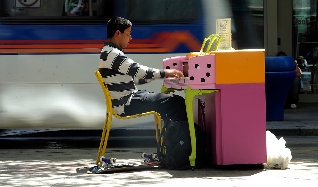 ". Michael Miller plays piano on the the 16th Street Mall Thursday, May 26, 2010.  10  colorfully painted pianos have been placed on the mall for the ""Keys to the City\"" a public piano art  program.   (Cyrus McCrimmon, The Denver Post)"