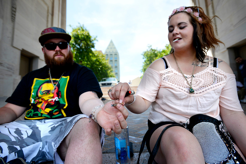 . Jon Dub passes a joint to Chelsea Barrigar at the Denver 420 Rally held Saturday at Civic Center Park. (Photo by Kira Horvath/ The Denver Post)