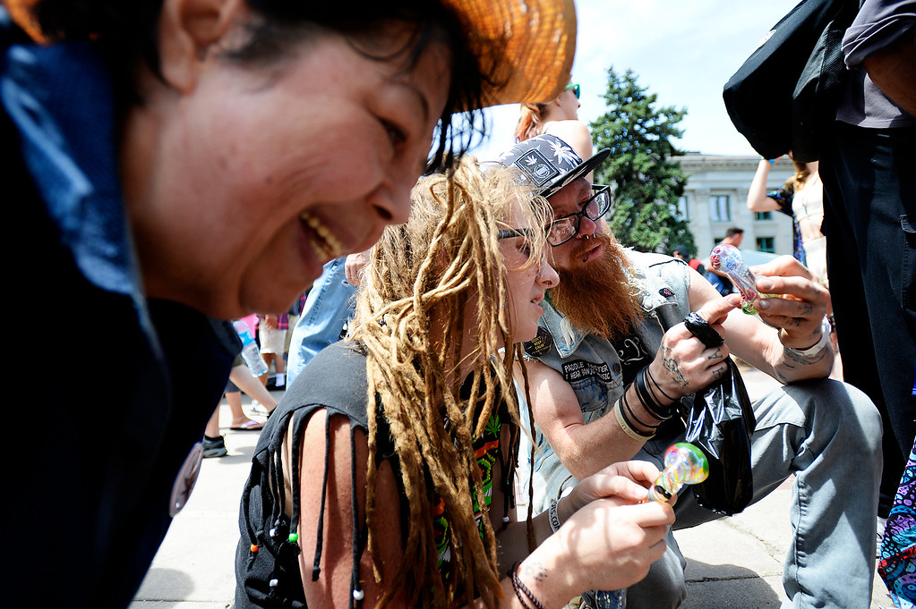 . From left, Sheila Brubaker, Krystal Quinn and Justin Campbell examine some glass pipes during the Denver 420 Rally held Saturday at Civic Center Park. (Photo by Kira Horvath/ The Denver Post)