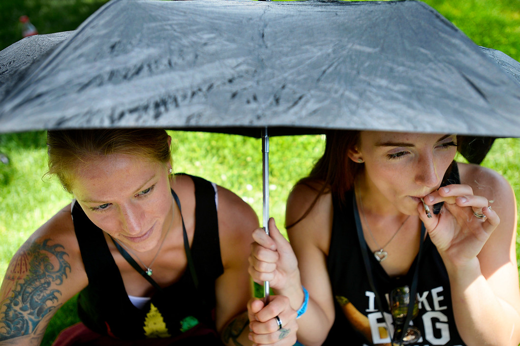 . Bekah Christine, left, and Vanessa Lee smoke marijuana under their umbrella during the Denver 420 Rally held Saturday at Civic Center Park. (Photo by Kira Horvath/ The Denver Post)