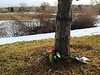 Fresh flowers rest against a tree Friday, January 15, 2016 near the pond in the background where three boys fell through ice Thursday evening. One teen died in the accident. (Photo by Kenneth D. Lyons/The Denver Post)