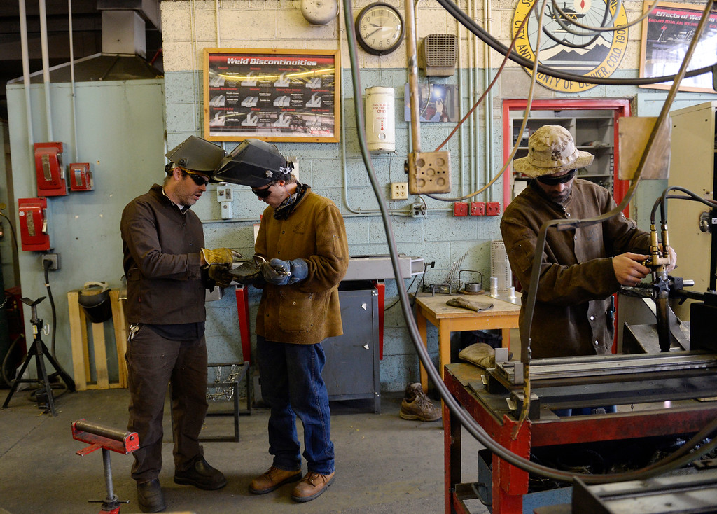 . Instructor Matt Sartorio, left, helps student Taylor Smith while other student Justin Alley, right, uses a track cutter in the welding class in the welding lab at Emily Griffith Technical College  in Denver on Wednesday, October 8,  2014.  (Denver Post Photo by Cyrus McCrimmon)